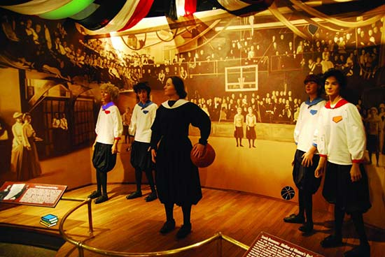 women figurines in vintage basketbal outfits with ball with sepia vintage photo beckground on museum stage